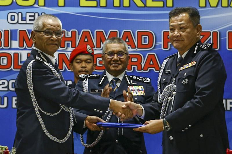 Datuk Abdul Hamid Bador (right) shakes hands with outgoing deputy inspector-general Tan Sri Noor Rashid Ibrahim during the handover ceremony at the Central Police Training Centre in Kuala Lumpur March 15, 2019. — Picture by Hari Anggara