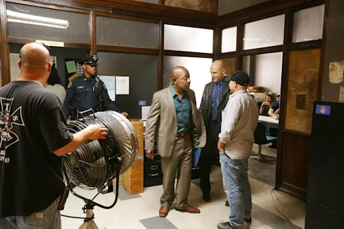 "In this May 20, 2013, photo, actors Lennie James, center, and Mark Strong, second from right, talk with director Andrew Bernstein, right, during a break in the filming of ""Low Winter Sun"" in Detroit. The series, premiering Sunday, Aug. 11, revives a two-part U.K. miniseries from 2006. It also marks Hollywood's return to the Motor City as a place to explore crime, following ABC's ""Detroit 1-8-7."" It aired during the 2010-11 season. (AP Photo/Carlos Osorio)"