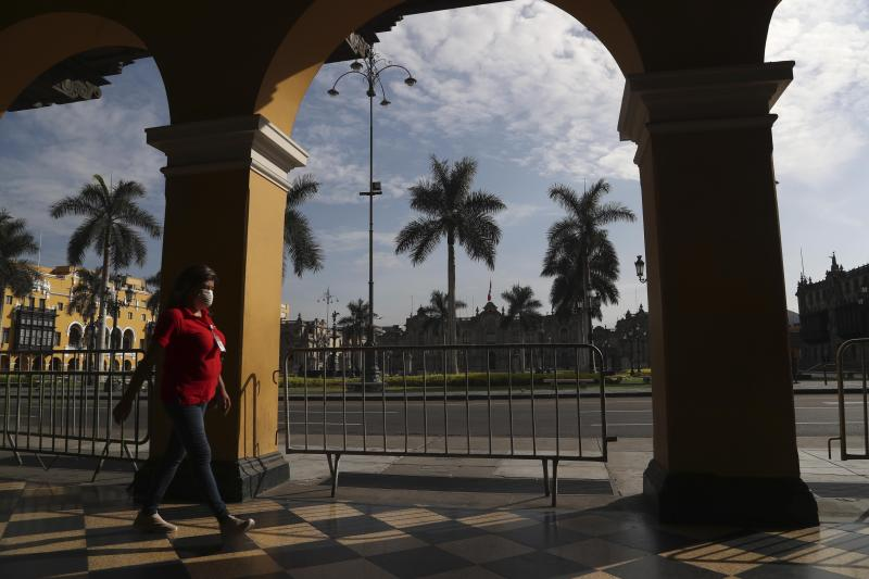 A woman, wearing a mask as a preventive measure against the spread of the new coronavirus, walks through an empty Plaza de Armas de Lima in downtown Lima, Peru, March 18, 2020. (AP Photo/Martin Mejia)