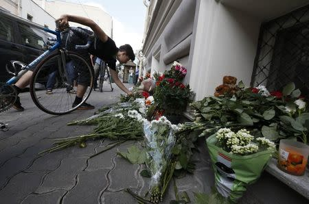 A man places flowers outside the Dutch embassy in Moscow
