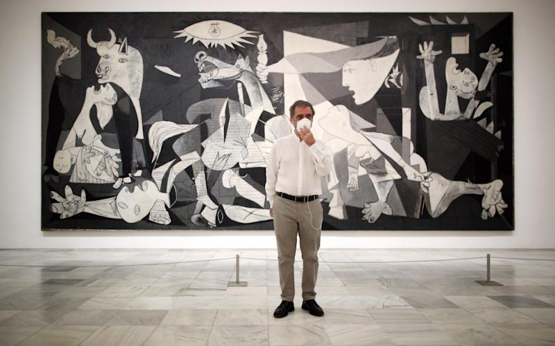 The director of the Reina Sofia Museum, Manuel Borja-Villel, poses next to Pablo Picasso's painting 'Guernica' - Getty