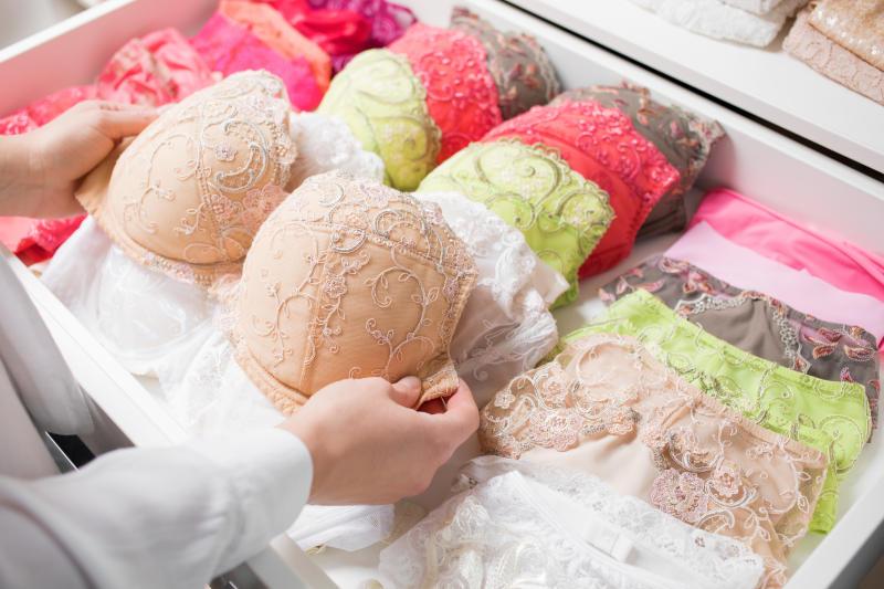 Woman organizing bras and underwear in drawer
