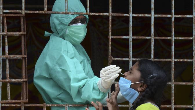 Seorang petugas kesehatan mengumpulkan sampel usap dari seorang gadis untuk menguji virus Corona Covid-19 di daerah kumuh di Hyderabad (23/9/2020). (AFP/Noah Seelam)