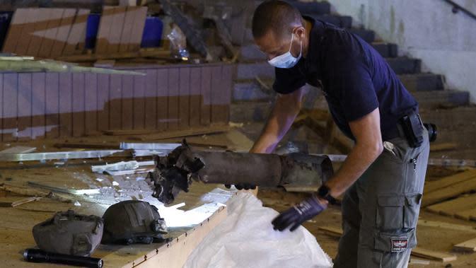Pasukan keamanan Israel memeriksa sisa-sisa roket yang ditembakkan dari Jalur Gaza dan jatuh di Kota Ashdod, Selasa (15/9/2020). Serangan yang terjadi saat Israel menandatangani kesepakatan normalisasi dengan Bahrain dan UEA ini mengakibatkan dua orang terluka. (JACK GUEZ/AFP)