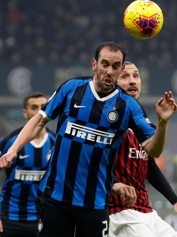 Bek veteran Inter Milan, Diego Godin berebut bola dengan striker AC Milan, Zlatan Ibrahimovic, pada laga pekan ke-23 Serie A di Giuseppe Meazza, Minggu (9/2/2020). Sempat tertinggal, Inter Milan sukses mengemas kemenangan 4-2 dari rival sekota AC Milan. (AP/Antonio Calanni)