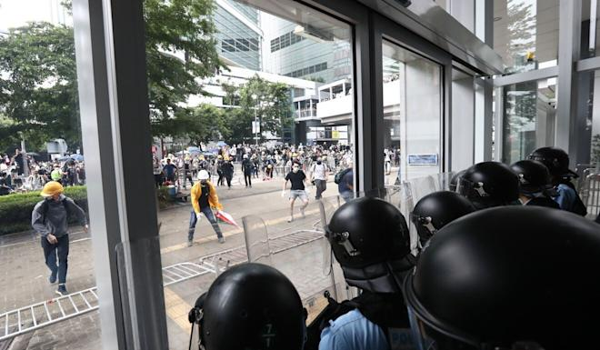 Crowds outside Legco brandish umbrellas as Hong Kong riot police wait inside Legco on June 12, 2019. Photo: Nora Tam