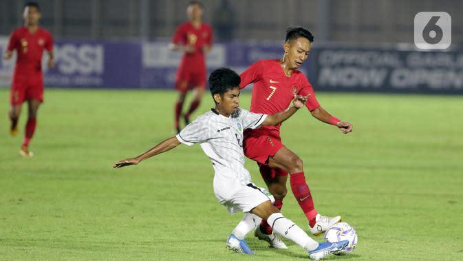 Pemain Timnas Indonesia U-19, Beckham Putra Nugraha (kanan) berebut bola dengan pemain Timor Leste pada laga kualifikasi Grup K Piala AFC U-19 2020 di Stadion Madya Gelora Bung Karno, Jakarta, Rabu (6/11/2019). Indonesia unggul 3-1. (Liputan6.com/Helmi Fithriansyah)