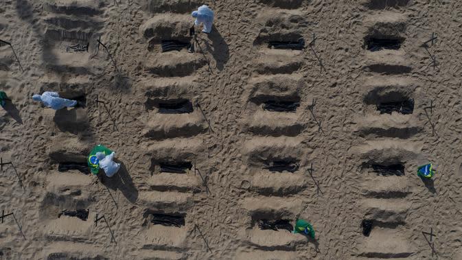 Aktivis LSM Rio de Paz menggali kuburan sebagai bentuk protes di pantai Copacabana, Rio de Janeiro, Kamis (11/6/2020). Kuburan-kuburan dengan simbol salib hitam yang dihiasi bendera Brasil kecil itu untuk mengenang puluhan ribu pasien corona yang meninggal di negara tersebut. (AP Photo/Leo Correa)
