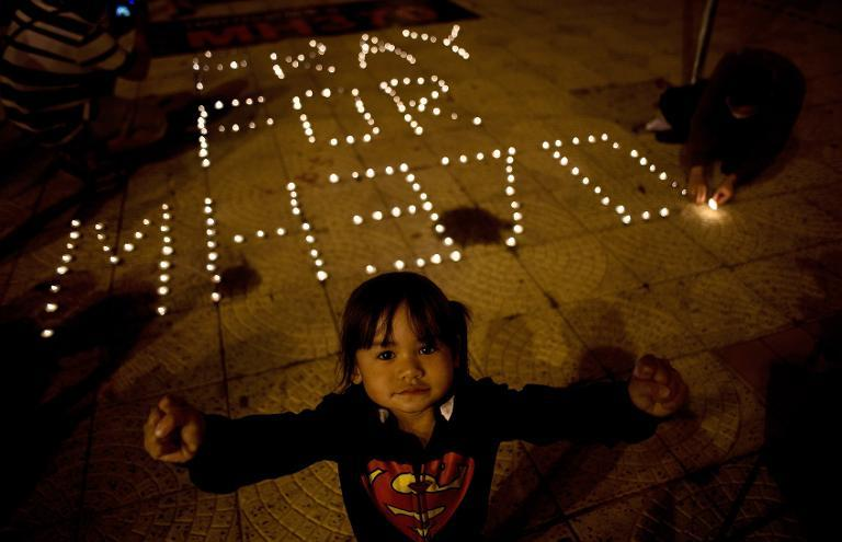 A Malaysian ethnic Chinese child reacts to the camera as others light candles during a vigil for missing Malaysia Airlines passengers at the Independence Square in Kuala Lumpur on March 10, 2014