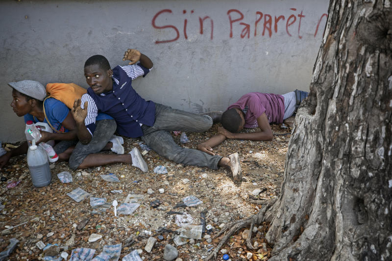 People take cover after presidential guards opened fire to disperse mourners after clashing with protesters attending a public funeral for two people killed in recent protests, in Port-au-Prince, Haiti, Oct. 16, 2019. The image was part of a series of photographs by Associated Press photographers which was named a finalist for the 2020 Pulitzer Prize for Breaking News Photography. (AP Photo/Rebecca Blackwell)