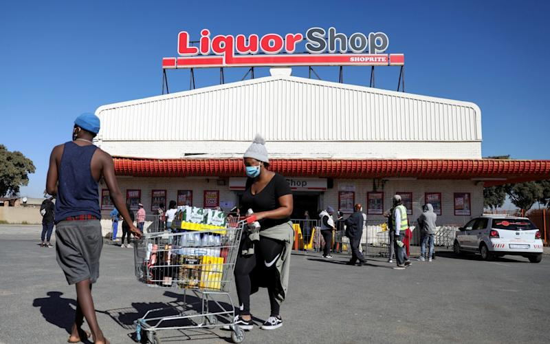 People wearing protective face masks walk with a trolley full of alcohol in front of a liquor store as South Africa lifts a lockdown lasting two months, to try to revive the economy amid the spread of the coronavirus disease (COVID-19), in Soweto, South Africa June 1, 2020. - Siphiwe Sibeko/Reuters