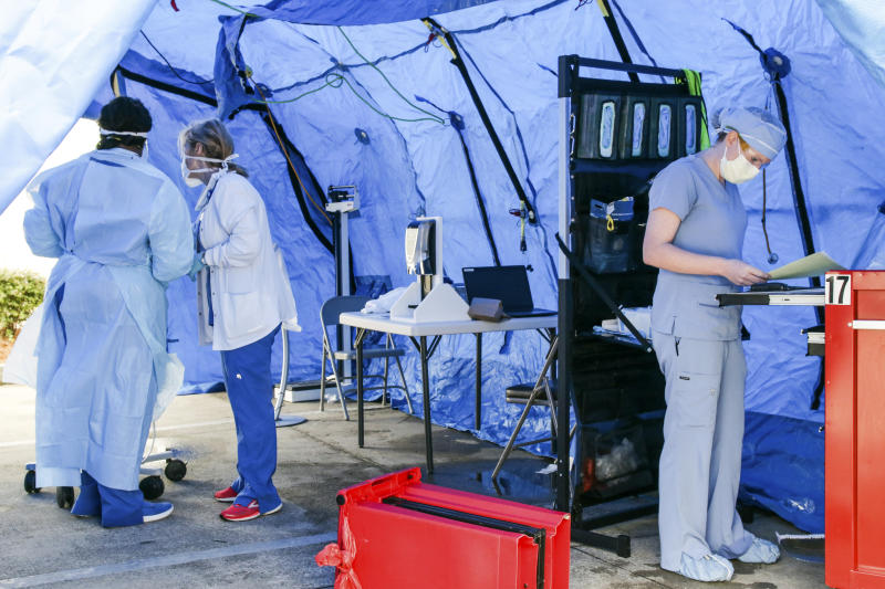 Nurses from Rush Health Systems in Meridian, Miss., set up a triage area to help keep too many people from entering the emergency room area at the hospital Tuesday, March 31, 2020. Rush wants the public to know that this is not a COVID-19 drive-through testing sight. (Paula Merritt/The Meridian Star via AP)