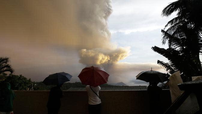 Sejumlah orang menyaksikan Gunung Api Taal erupsi di Tagaytay, Provinsi Cavite, Filipina, Minggu (12/1/2020). Gunung Api Taal mengeluarkan awan abu mencapai 50.000 kaki (15.000 meter) ke atmosfer. (AP Photo/Aaron Favila)