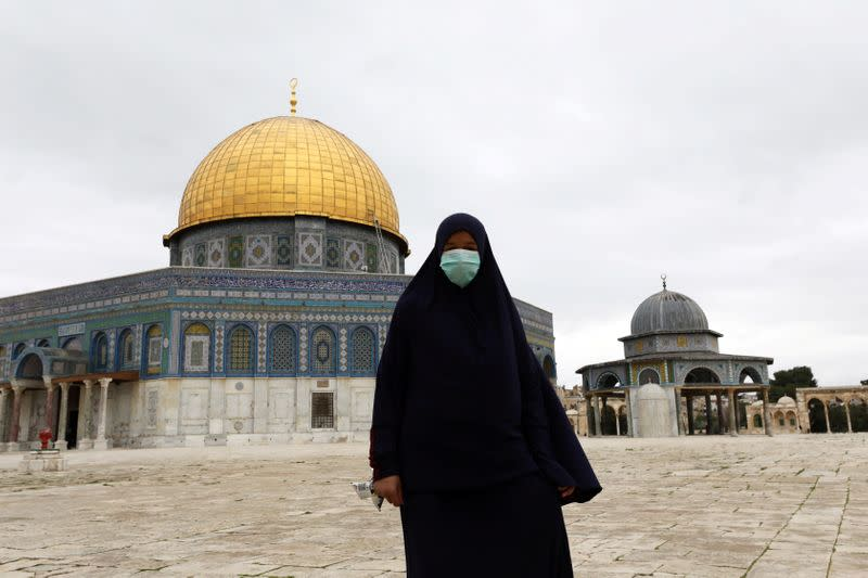 FILE PHOTO: A worshipper wearing a mask walks in front of the Dome of the Rock in the compound known to Muslims as Noble Sanctuary and to Jews as Temple Mount, in Jerusalem's Old City