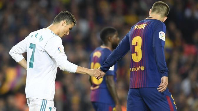 Gerard Pique (kanan, Barcelona) dan Cristiano Ronaldo (kiri, Real Madrid) menunjukkan respek pada laga di Camp Nou, Minggu (6/5/2018). (AFP/Lluis Gene)