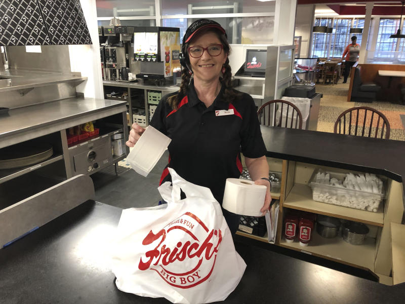 In this photo made on March 20, 2020, Frisch's Big Boy restaurant employee Nicole Cox bags up an order of toilet paper, among in-demand items including milk and bread the double-decker burger chain is now offering during the coronavirus outbreak in Cincinnati, Ohio.  With business sinking under coronavirus outbreak restrictions,the nation's restaurants are transforming operations and menus to try to stay afloat. (AP Photo/Dan Sewell)