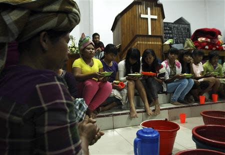 Villagers pray before taking their dinner inside a church used as temporary shelter as a safety precaution after Sinabung volcano erupted at Payung village in Karo district, Indonesia's north Sumatra province