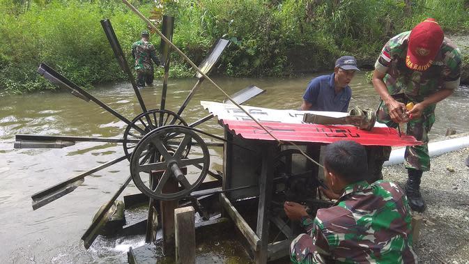 Perawatan kincir air di Kampung Kriku yang membuat adanya energi terbarukan untuk sumber listrik. (Liputan6.com/Katharina Janur)