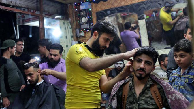 Sejumlah pria mencukur rambut jelang Hari Raya Idul Fitri di Kota Idlib, Suriah, Jumat (22/5/2020). Umat muslim seluruh dunia bersiap menyambut Idul Fitri yang sekaligus menandai berakhirnya bulan suci Ramadan. (OMAR HAJ KADOUR/AFP)