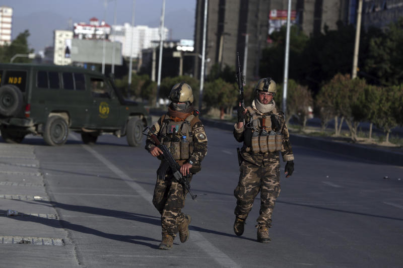 Afghan security forces inspect the site where a bus carrying local TV station employees hit a roadside bomb in Kabul, Afghanistan, Saturday, May 30, 2020. (AP Photo/Rahmat Gul)