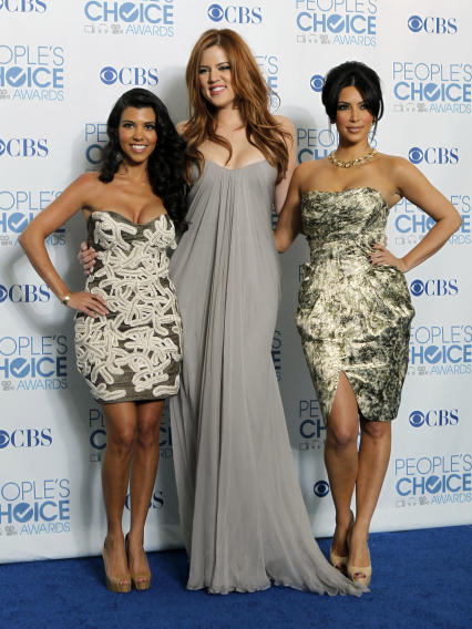 "FILE - In this Jan. 5, 2011 file photo, from left, Kourtney Kardashian, Khloe Kardashian, and Kim Kardashian pose for a photo backstage with the award for favorite TV guilty pleasure for ""Keeping Up with the Kardashians"" at the People's Choice Awards in Los Angeles. A Central California judge has thrown out a lawsuit filed against the Kardashian sisters after they pulled their endorsement of a prepaid debit card that drew criticism for its high  fees. (AP Photo/Matt Sayles, file)"