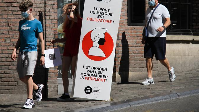 Sejumlah orang berjalan melewati spanduk informasi yang mengingatkan masyarakat untuk mengenakan masker di Brussel, Belgia (5/8/2020). Kota Brussel memperluas aturan wajib pakai masker di wilayahnya hingga termasuk di jalan-jalan yang ramai dan zona pejalan kaki. (Xinhua/Zheng Huansong)