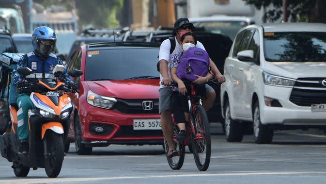 Sepasang warga menaiki sepeda di jalanan kota Manila pada 20 Mei 2020. Alat transportasi umum yang masih beroperasi dalam kapasitas terbatas membuat warga Filipina beralih ke sepeda saat berakhirnya masa karantina dan dimulainya periode The New Normal. (Ted ALJIBE/AFP)