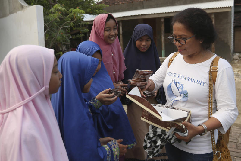 Ni Luh Erniati, right, gives cakes to Ali Fauzi's daughter and relatives while visiting Fauzi's home in Tenggulun, East Java, Indonesia, on Saturday, April 27, 2019. Erniati, whose husband was killed in the 2002 Bali bombings, and Fauzi, a former bombmaker whose brothers helped orchestrate the Bali attack, have reconciled as part of a peacebuilding program bringing together ex-terrorists and victims. (AP Photo/Tatan Syuflana)