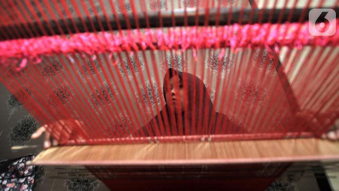Warga menyelesaikan pembuatan tenun saat Pelatihan Tenun Betawi di Rusun Jatinegara Barat, Jakarta, Rabu (6/11/2019). Dalam pelatihan ini warga dilatih membuat tenun dengan tema ornamen budaya Betawi. (merdeka.com/Iqbal Nugroho)