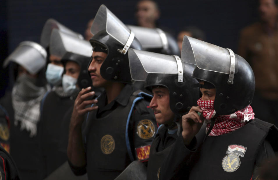 Egyptian riot police take positions during clashes with anti-government protesters, not seen, near Tahrir Square in Cairo, Egypt, Wednesday, Jan. 30, 2013. Egypt's liberal opposition leader called for a broad national dialogue with the Islamist government, all political factions and the powerful military on Wednesday, aimed at stopping the country's eruption of political violence that has left scores dead in the past week. (AP Photo/Khalil Hamra)