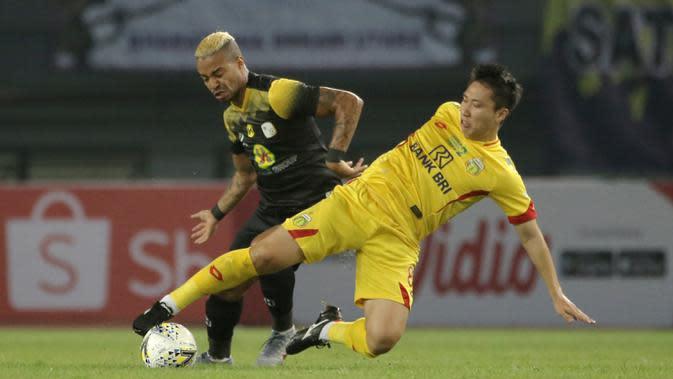 Gelandang Bhayangkara FC, Lee Yoo-joon, berebut bola dengan bek Barito Putera, Ronny Beroperay, pada laga Liga 1 2019 di Stadion Patriot, Bekasi, Selasa (29/5). Bhayangkara menang 4-2 atas Barito. (Bola.com/Yoppy Renato)