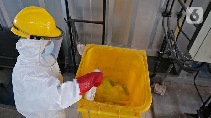 Petugas membersihkan tempat sampah dengan cairan disinfektan usai melakukan proses pembakaran limbah medis ke dalam incinerator di RSCM Jakarta, Jumat (26/6/2020). Volume limbah medis infeksius di seluruh Indonesia hingga 8 Juni 2020 mencapai lebih dari 1.100 ton. (Liputan6.com/Herman Zakharia)