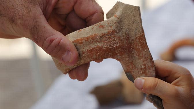 Seorang arkeolog menunjukkan sebuah stempel bertuliskan huruf Ibrani kuno yang ditemukan di sebuah situs penggalian di Yerusalem (22/7/2020). Tim arkeolog Israel menemukan pusat penyimpanan administratif berusia 2.700 tahun di Yerusalem. (Xinhua/Gil Cohen Magen)