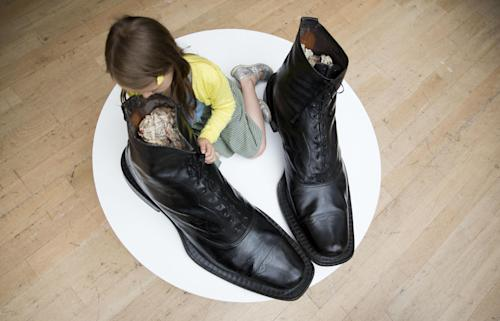 """Riva aged 6, poses for photographs beside a pair of large-scale Victorian leather """"Ivy Brand"""" Exhibition Balmoral boots, circa 1880, during a photocall at Christie's auction house in London, Monday, Aug. 5, 2013. The boots, are estimated to fetch between 10,000 and 12,000 pounds ($15,352 to $18,423 and 11,564 to 13,876 euro) in an """"Out of the Ordinary"""" sale on September 5. (AP Photo/Matt Dunham)"""
