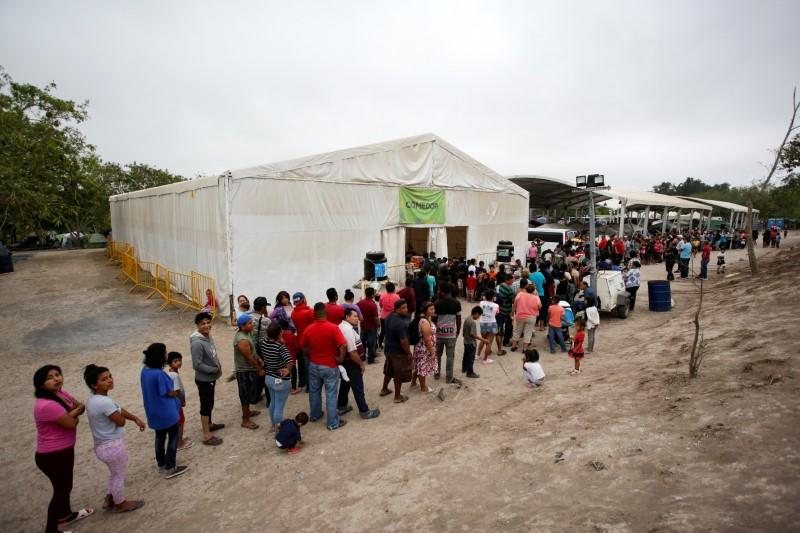 Migrants seeking asylum in the U.S. queue for food at an encampment of more than 2,000 migrants, as local authorities prepare to respond to the coronavirus disease (COVID-19) outbreak, in Matamoro
