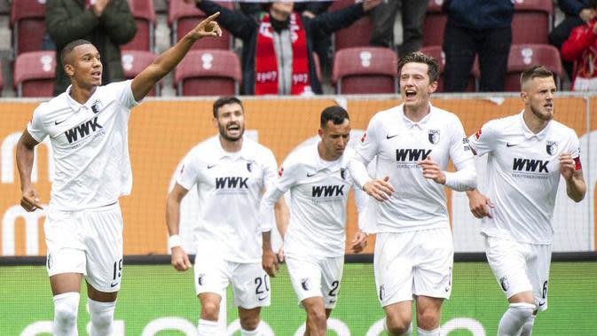 Pemain Augsburg, Felix Uduokhai, melakukan selebrasi usai mencetak gol ke gawang Borussia Dortmund pada laga Bundesliga, Minggu (27/9/2020). Augsburg menang dengan skor 2-0. (Matthias Balk/dpa via AP)