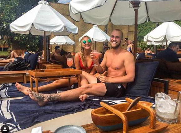Luke Bevan and Tova Ronnersjö relax on sun-chairs wearing bathers.