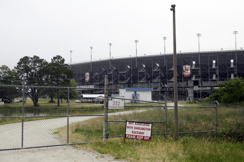 A gate is locked outside Darlington Raceway Sunday, May 17, 2020, in Darlington, S.C. NASCAR, which has been idle since March 8 because of the coronavirus pandemic, makes its return at the track with the Real Heroes 400 Nascar Cup Series auto race Sunday. (AP Photo/Brynn Anderson)