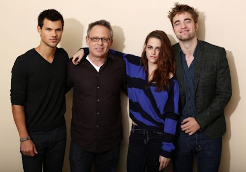 "In this Thursday, Nov. 1, 2012 photo, from left, actor Taylor Lautner, director Bill Condon, actress Kristen Stewart, and actor Robert Pattinson, from the upcoming film ""The Twilight Saga: Breaking Dawn Part 2,"" pose for a portrait in Los Angeles. Condon, who began working with Stewart, Pattinson and Taylor Lautner in 2010, says the young megastars understand the pressures of the spotlight. ""They didn't get altered by it, which is kind of extraordinary,"" he said. (Photo by Matt Sayles/Invision/AP)"