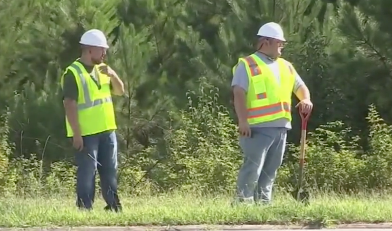 Undercover Atlanta police officers are seen posing as construction workers in high-visibility vests and hard hats at the side of the road.