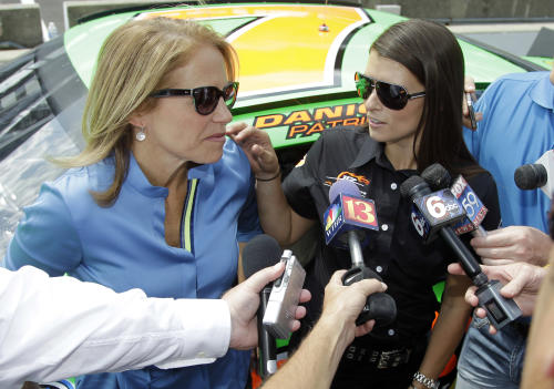 Race car driver Danica Patrick, right, and journalist/television personality Katie Couric are interviewed at the Indianapolis Motor Speedway in Indianapolis, Tuesday, July 10, 2012. Patrick gave Couric a tour of the Speedway and a ride in a two-seat race car. (AP Photo/Michael Conroy)