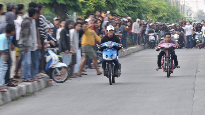 Dua pembalap beradu kecepatan saat ikut dalam balapan liar di Jakarta, Minggu (27/5) pagi. Balapan liar masih menjadi kegiatan favorit remaja di Ibu Kota dalam menghabiskan waktu Minggu pagi di bulan Ramadan. (Merdeka.com/Iqbal S Nugroho)
