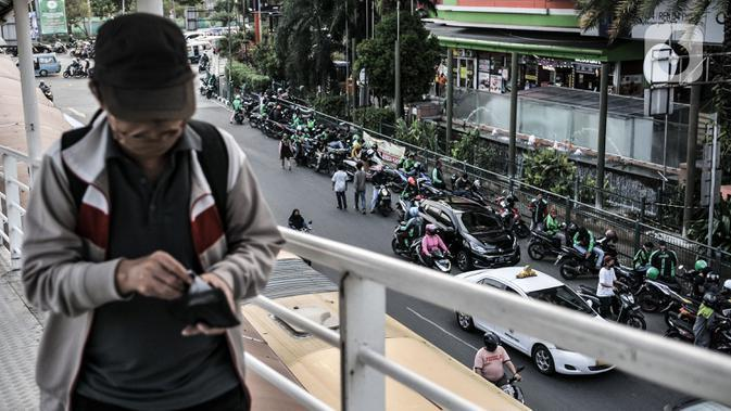 Pengemudi ojek online (ojol) memenuhi bahu jalan saat menunggu penumpang di kawasan Cililitan, Jakarta, Rabu (16/9/2020). Pemprov DKI Jakarta telah melarang ojol dan ojek pangkalan berkumpul lebih dari lima orang serta menjaga jarak sepeda motor minimal dua meter. (merdeka.com/Iqbal S. Nugroho)