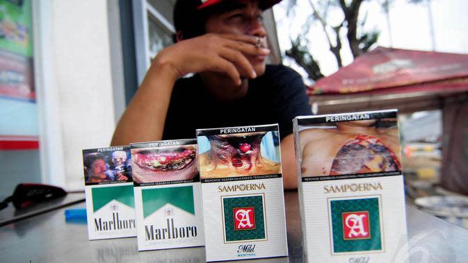 Seorang perokok tampak menunjukan bungkus rokok yang telah berganti peringatan bergambar di minimarket, Jakarta, Selasa (24/6/14). (Liputan6.com/Faizal Fanani)