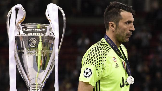 Kiper Juventus, Gianluigi Buffon, tampak sedih ketika melewati piala Liga Champions di Stadion Millennium, Sabtu (3/6/2017). Juventus kalah 1-4 dari Real Madrid. (AFP/Javier Soriano)