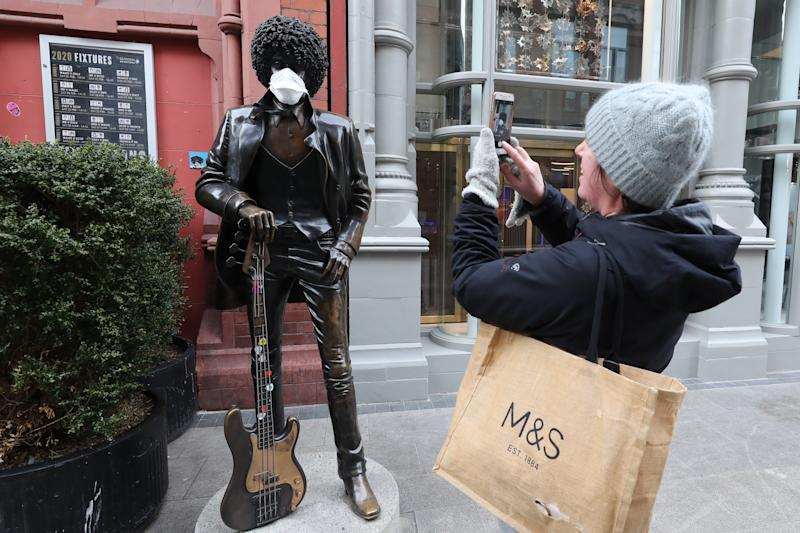 People taking photos of the Phil Lynott Statue dressed up in a face mask off Grafton Street in Dublin, as NHS England announced that the coronavirus death toll had reached 137 in the UK. (Photo by Niall Carson/PA Images via Getty Images)