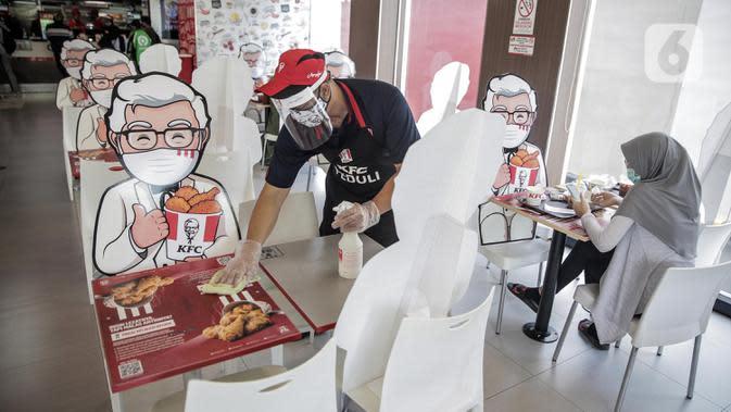 Pelayan membersihkan meja yang diberi pembatas banner bergambar karakter di KFC Salemba, Jakarta, Selasa (23/6/2020). Banner bergambar tersebut berguna untuk pembatas bagi pengunjung yang makan di tempat saat fase kenormalan baru. (Liputan6.com/Faizal Fanani)