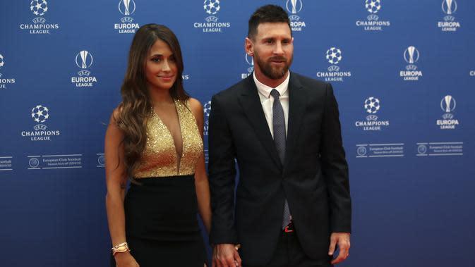 Penyerang Barcelona, Lionel Messi bersama istrinya Antonella Roccuzzo berpose saat tiba menghadiri acara undian penyisihan grup Liga Champions UEFA dan pemain terbaik Eropa di Forum Grimaldi, Monaco (29/8/2019). (AP Photo/Daniel Cole)