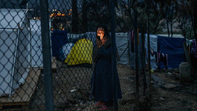 Seorang wanita imigran berbicara di telepon genggamnya di luar kamp pengungsi di pulau Samos, Yunani (13/11/2019). Ribuan imigran berjuang untuk menemukan ruang di perbukitan di atas kota, membuat rumah sementara dari bahan bangunan apa pun yang dapat mereka temukan. (AFP Photo/Angelos Tzortzinis)