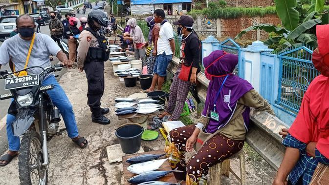 Polisi di Kota Jayapura sosialisasi pencegahan corona kepada pedagang ikan dadakan di Dok VIII Jayapura. (Liputan6.com/Katharina Janur/Polresta Jayapura Kota)